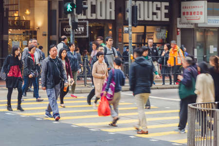 Crowds of people walk across the downtown street of Hong Kong.  Asian people cross the road on a zebra. Hong Kong, 2018-03-06