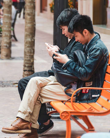 Two young Asian guys use mobile phones in a park or city.  Concept of addiction on gadgets of youth generation Z. Hong Kong, 2018-03-06