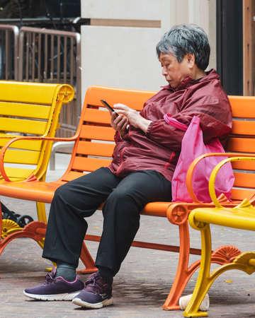 Asian elderly woman uses a smartphone on a bench in the city.  Hong Kong,  2018-03-06 Redakční