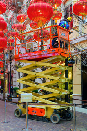 Electrician on a hydraulic scissor lift serves a street lamp.  Around the decoration of Chinese lanterns. Hong Kong, 2018-03-06