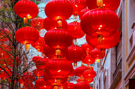 Rows of Chinese lanterns in an alley between buildings Archivio Fotografico