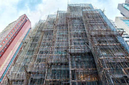 Renowation of  building  facade  with scaffolding. Construction of high-rise building