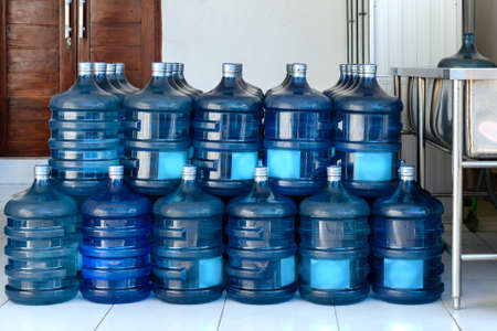 Row of large bottles of drinking water  for the cooler. Water delivery. Packed and ready to be sent to customers.