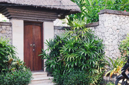 view of the front door in a stone fence surrounded by green plants.  Housing villa in the tropics. Bali, Indonesia Reklamní fotografie