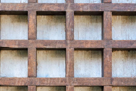 Old wooden cells on a white wall. Vintage brown background.