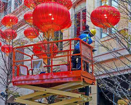 Electrician on a hydraulic scissor lift is serving a street lamp. Around the decoration of Chinese lanterns