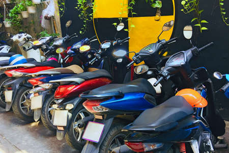 Motorbikes in a row in a parking lot near a colored wall. Transport is not claimed during quarantine