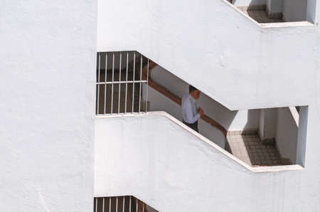 White wall with a balcony.  Blurred man descends the stair flight. Minimal urban style. Hong Kong 免版税图像