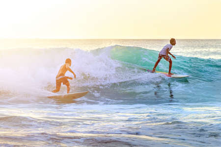 Two surfers ride on boards on turquoise waves in the backlight. Bali, 2018-04-21