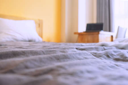 Blurred photo of a bed with a laptop on the table. Workplace in a small apartment. Photo with selective focus 免版税图像
