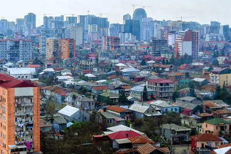 Top view of dense city building. Dense development in poor countries. Overpopulation concept. Houses in the private sector behind the wall of skyscrapers. Batumi, Georgia.
