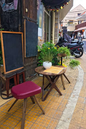 A small street cafe is open and waiting for its visitors. Empty place for text, copy space.  Vertical photo 免版税图像