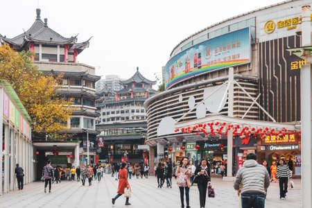 Traditional chinese architecture of the old part of the city. People walking on busy street. Urban city daily life background. Shenzhen, China, 2018-03-08