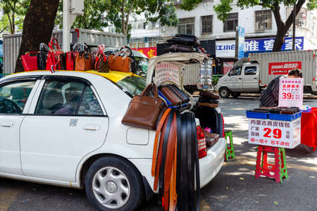 Car, as a counter for the sale of leather goods, bags and belts. City street market. Shenzhen, China, 2018-03-12 新闻类图片