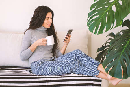 Beautiful caucasian brunette woman browsing mobile phone and drinking coffee while resting on sofa at home surrounded by plants. Social networks addiction concept.