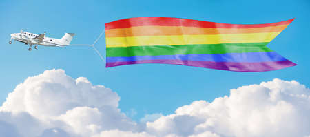 Rainbow LGBT flag among the clouds tug by airplane in the sky.  Support and tolerance for sexual minorities concept. Banque d'images