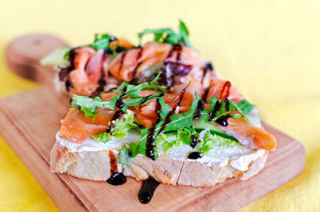 Sandwich with red fish,  cheese and arugula on a board.  Selective soft focus. Copy space 免版税图像