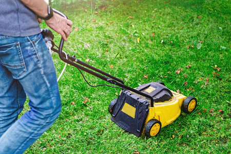 Man moving a lawn mower to cut the grass on the lawn.  Sunny autumn day.  Gardening work tool.  Photo with blur in motion and soft focus.  Empty place for text, copy space.