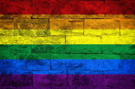 Rainbow flag painted on a brick wall. Gay pride support concept