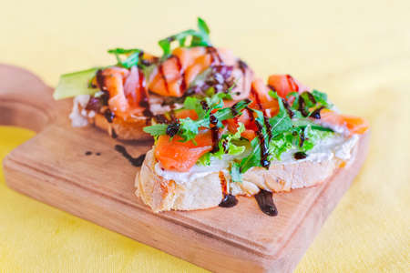 Bruschetta with salmon on a wooden board. Side view. Photo with selective soft focus.  Empty place for text, copy space. 免版税图像