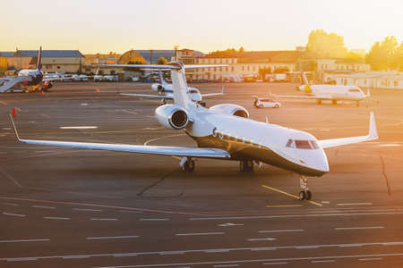 Private jet aircraft at airport. Illuminated by the sun at sunset. Top and side view.