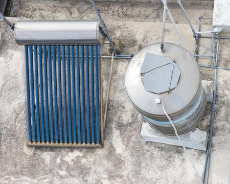 Solar water heating system with collector at roof.  Green energy for everyday life 免版税图像