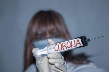 Coronavirus vaccine. Doctor woman (blurred) holding syringe and needle with corona virus written. Medical specialist are trying to find a cure to fight COVID - 19 and stop pandemic. Corona isolated. Imagens
