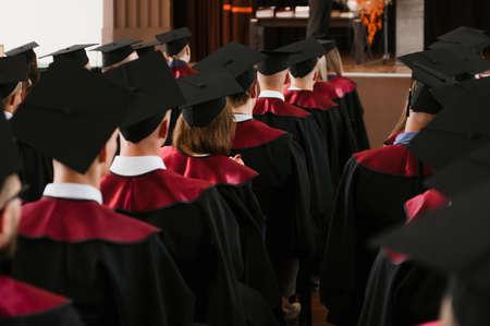 小组新鲜的大学毕业生与长袍和帽子在仪式上