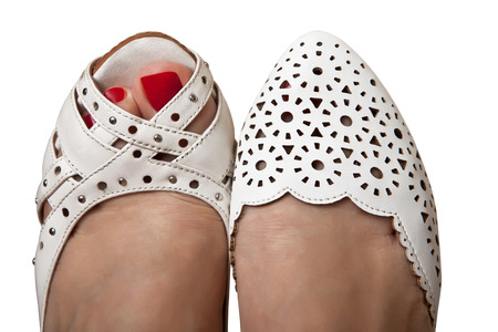 women's issues: Womens feet in summer shoes white Stock Photo