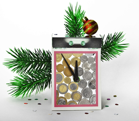 Tear-off calendar with clock and coins of different countries on a white background with branches of Christmas tree and confetti. Imagens