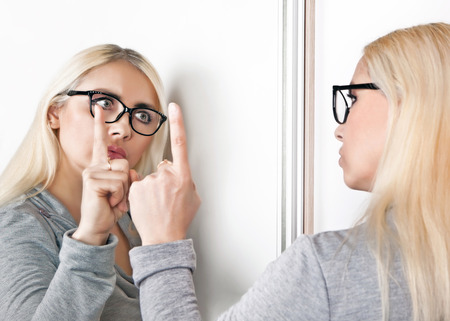 A woman talks to her reflection in front of a mirror.