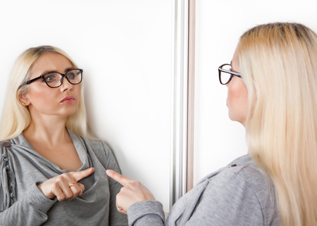 A woman pokes a finger at his reflection in the mirror.
