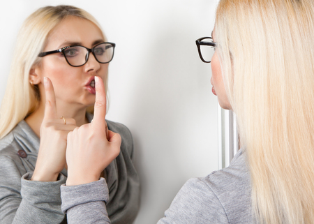 A woman close her mouth in front of her mirror. A sign of silence. Stock Photo