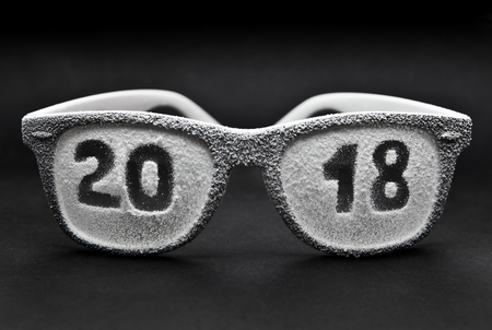 Glasses covered with artificial snow with the inscription 2018, on a black background