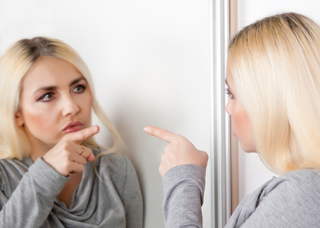 A woman points her finger at her reflection in the mirror.