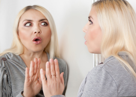 A woman with a fear and looks looks at her reflection in the mirror