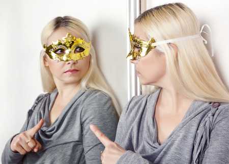 Woman in carnival mask pointing finger at his reflection in the mirror