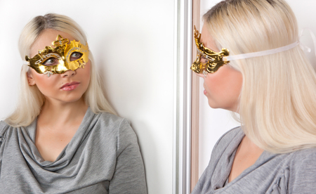 A woman in a carnival gold mask with a dream looks thoughtfully at her reflection in the mirror.