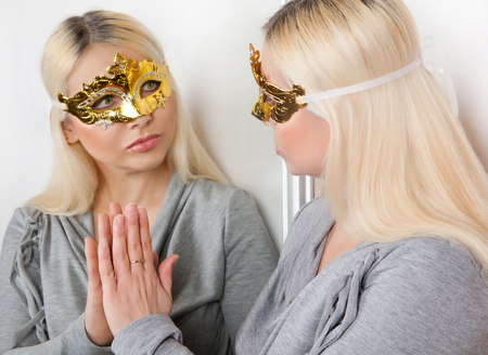 Masked woman touches her hand reflection in the mirror. Stock Photo