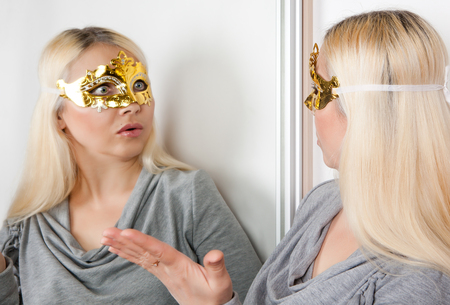The masked woman stares at her reflection in the mirror. Stock Photo