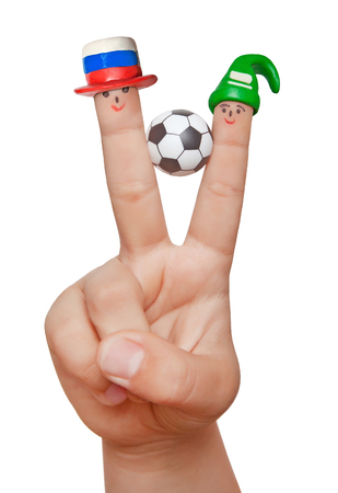 Two fingers in plasticine capsules with a soccer ball, isolated on a white background. Fans of Russia and Saudi Arabia.