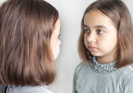 Teen girl looks at her reflection in the mirror.