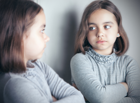 A teenage girl in a gray jacket looks at her reflection in the mirror. Imagens