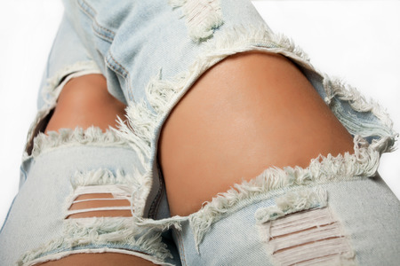 Legs in ripped blue jeans on white close up background.
