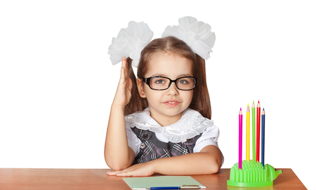 The schoolgirl of the first class with white bows with glasses is sitting behind his desk, raising his right hand. Isolated on white background. Imagens