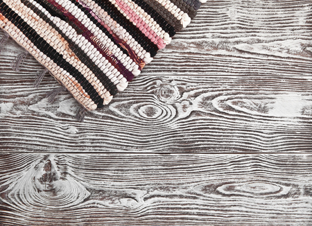 Wooden background with white coating and hanging corner rustic rug.