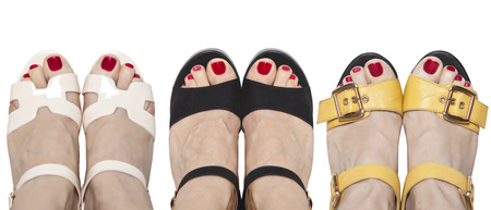 Three pairs of legs in sandals. The problem of choice of footwear. Imagens