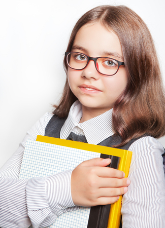 Portrait of teenage girl with glasses with books on white background. Imagens