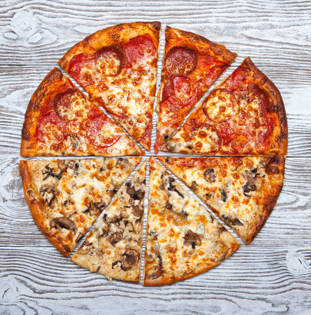 Pizza two in one vegetarian mushroom and meat on a wooden table. Oct.13, 2018 Edit | Remove 219890322 Pizza without one piece, vegetarian mushroom and meat on a wooden table.