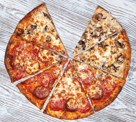 Pizza without one piece, vegetarian mushroom and meat on a wooden table.